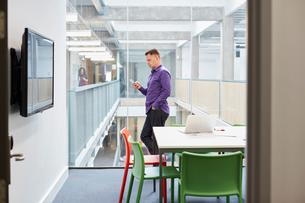 Male designer reading smartphone update in design studioの写真素材 [FYI03555419]