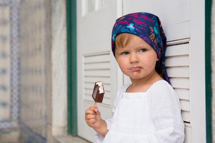 Portrait of female toddler leaning against shutters eating ice lolly, Beja, Portugalの写真素材 [FYI03555463]