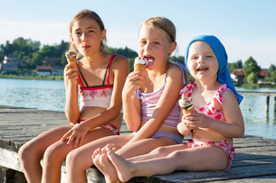 Two sisters and female toddler on pier eating ice cream cones, Lake Seeoner See, Bavaria, Germanyの写真素材 [FYI03555469]