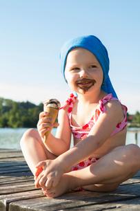 Portrait of female toddler on pier eating chocolate ice cream cone, Lake Seeoner See, Bavaria, Germaの写真素材 [FYI03555470]