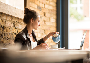 Young businesswoman pouring tea in cafeの写真素材 [FYI03555485]