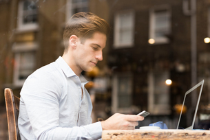 Window view of young businessman reading smartphone texts in cafeの写真素材 [FYI03555492]