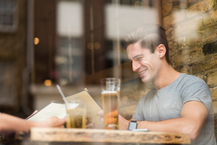 Window view of young man reading menu in restaurantの写真素材 [FYI03555504]
