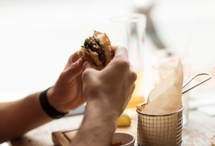 Hand of young man eating burger in restaurantの写真素材 [FYI03555508]