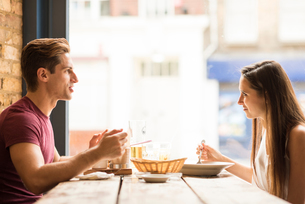 Young couple chatting whilst eating in restaurantの写真素材 [FYI03555509]