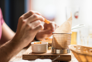Hand of young man eating chips in restaurantの写真素材 [FYI03555511]