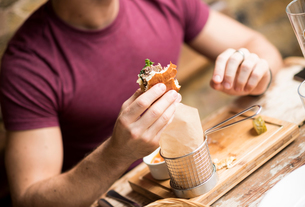 Cropped shot of young man eating burger in restaurantの写真素材 [FYI03555513]