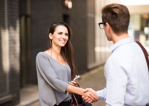 Young businessman and businesswoman shaking hands outside office, London, UKの写真素材 [FYI03555527]