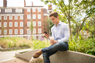 Businessman reading smartphone texts in city, London, UKの写真素材 [FYI03555534]