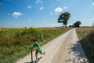 Boy speeding along rural road on scooter, Franceの写真素材 [FYI03555588]