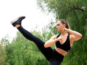 Young female kickboxer practicing kickboxing in parkの写真素材 [FYI03555634]