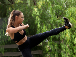 Young female kickboxer practicing kick in parkの写真素材 [FYI03555635]