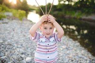 Portrait of cute boy holding sticks on his head at Lake Ontario, Oshawa, Canadaの写真素材 [FYI03555655]