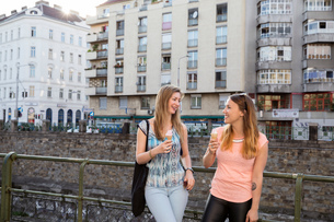 Two adult female friends eating ice cream cones and chatting in city, Vienna, Austriaの写真素材 [FYI03555682]