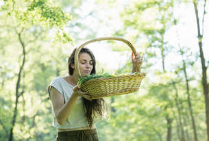 Young woman smelling foraged wild herbs in forest, Vogogna, Verbania, Piemonte, Italyの写真素材 [FYI03555714]