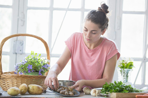 Young woman preparing snails at kitchen counter, Vogogna,Verbania, Piemonte, Italyの写真素材 [FYI03555725]