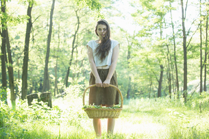Portrait of young woman foraging wild herbs in forest, Vogogna, Verbania, Piemonte, Italyの写真素材 [FYI03555729]
