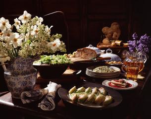 Traditional display of food; flowers in vase, roast lamb, potatoes, teddy bear, jug of beer, spaghetの写真素材 [FYI03555731]