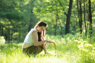 Young woman crouching to forage wild herbs in forest, Vogogna, Verbania, Piemonte, Italyの写真素材 [FYI03555733]