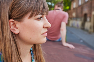 Young couple outdoors, sitting away from each other, sad expression on young woman's faceの写真素材 [FYI03555749]