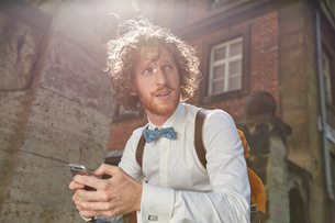 Young man outdoors, using smartphone, wearing shirt and bow tieの写真素材 [FYI03555754]