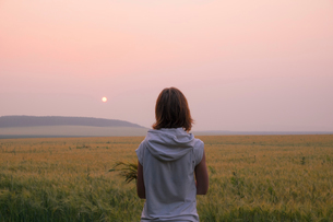 Woman standing in field watching sunset, rear view, Ural, Russiaの写真素材 [FYI03555820]