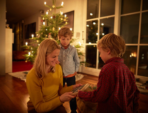 Mother and sons sitting at home at Christmas, exchanging giftsの写真素材 [FYI03555849]