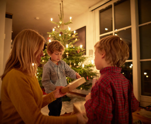 Mother and sons sitting at home at Christmas, exchanging giftsの写真素材 [FYI03555850]