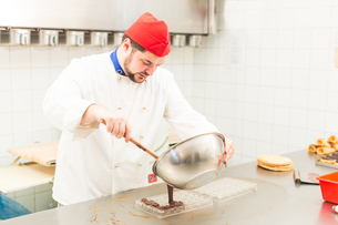 Chef pouring chocolate into chocolate mouldの写真素材 [FYI03555874]