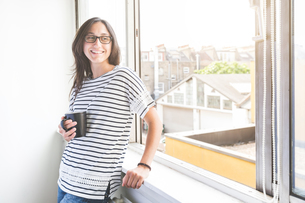 Woman in front of window holding coffee cup looking away smilingの写真素材 [FYI03555899]