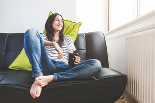 Woman sitting on sofa holding coffee cup looking out of window smilingの写真素材 [FYI03555902]
