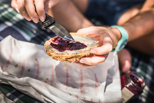 Close up of woman spreading jam on seeded bun, Meran, South Tyrol, Italyの写真素材 [FYI03555947]