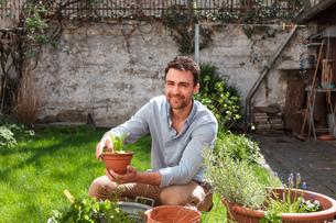 Man in garden tending to plantsの写真素材 [FYI03556065]
