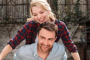 Man giving woman piggyback smilingの写真素材 [FYI03556071]