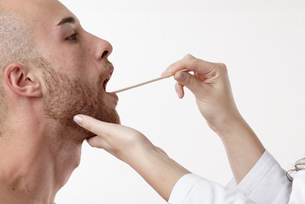 Doctor examining patients mouth with spatulaの写真素材 [FYI03556093]