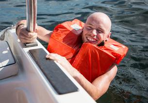Man wearing lifejacket in water looking at camera smilingの写真素材 [FYI03556112]