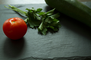 Tomato, courgette and parsley on slateの写真素材 [FYI03556141]