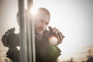Man in business attire behind corner at harbour poised with handgun, Cagliari, Sardinia, Italyの写真素材 [FYI03556215]