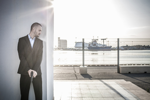 Man in business attire behind wall at harbour poised with handgun, Cagliari, Sardinia, Italyの写真素材 [FYI03556216]