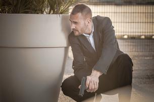 Man in business attire behind plant pot holding handgunの写真素材 [FYI03556218]