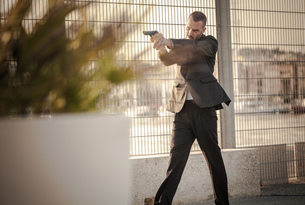 Man in business attire walking in harbour poised with handgun, Cagliari, Sardinia, Italyの写真素材 [FYI03556219]