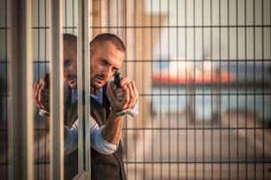 Man in business attire poised behind corner in harbour pointing handgun, Cagliari, Sardinia, Italyの写真素材 [FYI03556221]