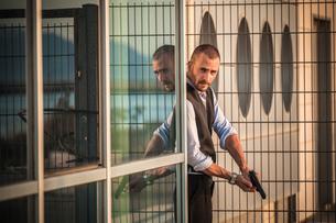 Man in business attire poised behind corner with handgun, Cagliari, Sardinia, Italyの写真素材 [FYI03556222]