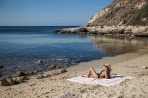 Young woman sunbathing on beach, Villasimius, Sardinia, Italyの写真素材 [FYI03556232]