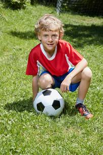 Portrait of boy wearing soccer uniform crouching with soccer ball in gardenの写真素材 [FYI03556242]