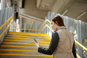 Rear view of young businesswoman reading smartphone texts on stairway, London, UKの写真素材 [FYI03556244]
