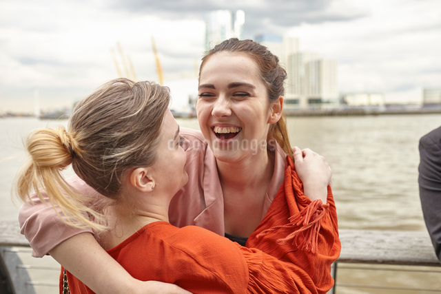 Two young businesswomen hugging on waterfront, London, UKの写真素材 [FYI03556262]