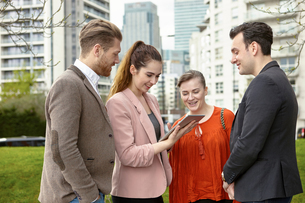 Businesswomen and businessmen looking at digital tablet outside office, London, UKの写真素材 [FYI03556275]