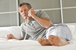 Senior man reclining on bed talking on landline telephoneの写真素材 [FYI03556292]