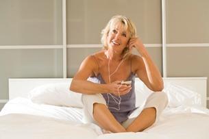 Mature woman sitting up in bed listening to earphonesの写真素材 [FYI03556294]